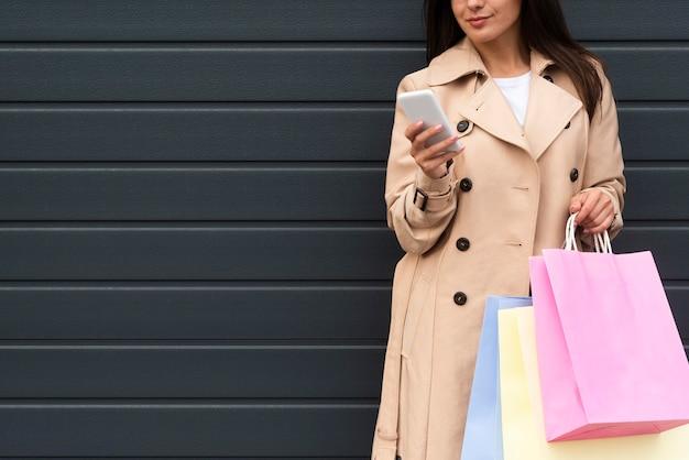 Vista frontal de la mujer al aire libre mirando el teléfono inteligente mientras agujerea las bolsas de la compra.
