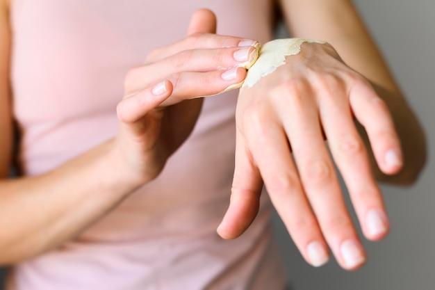 Vista frontal de la mujer aplicando loción en sus manos