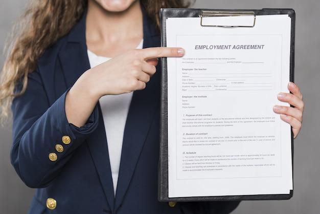 Vista frontal de la mujer apuntando al contrato para un nuevo trabajo