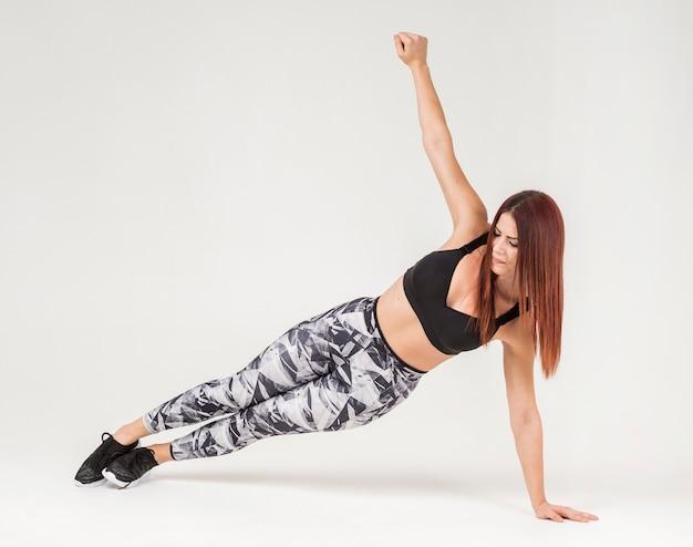 Vista frontal de la mujer atlética haciendo tablones de lado