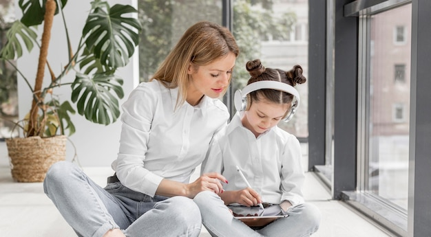 Vista frontal mujer ayudando a su hija con la tarea