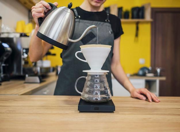 Vista frontal de la mujer barista vertiendo agua caliente sobre el filtro de café