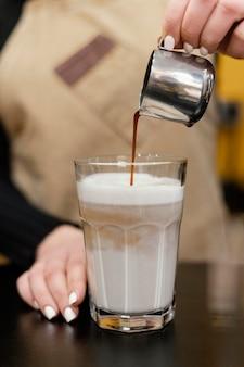 Vista frontal de la mujer barista vertiendo café en vaso de leche