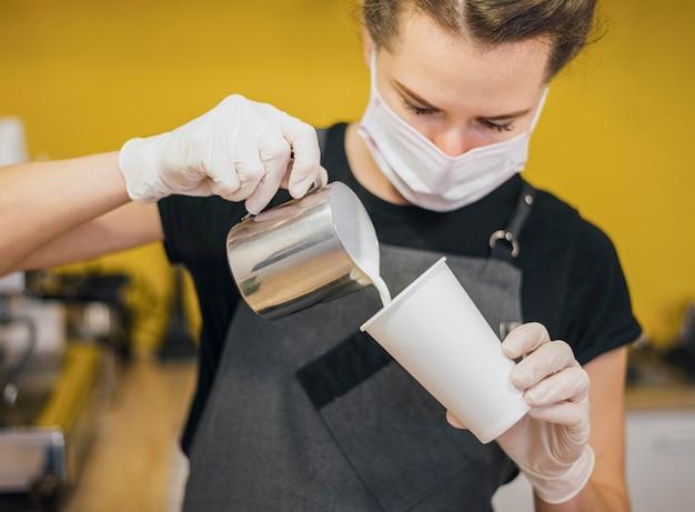 Vista frontal de la mujer barista vertiendo leche en la taza de café