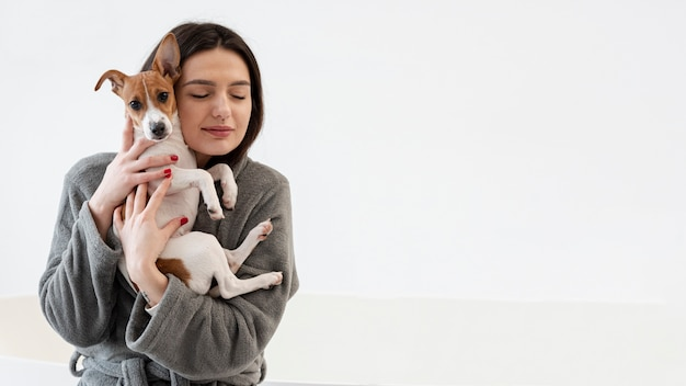 Vista frontal de la mujer en bata de baño con su perro