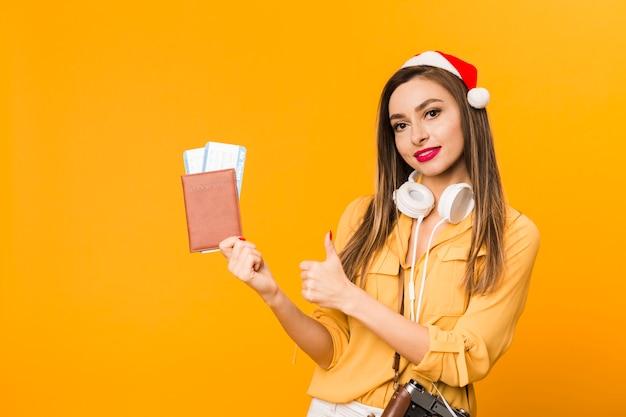 Vista frontal de la mujer con billetes de avión y pasaporte dando pulgares arriba