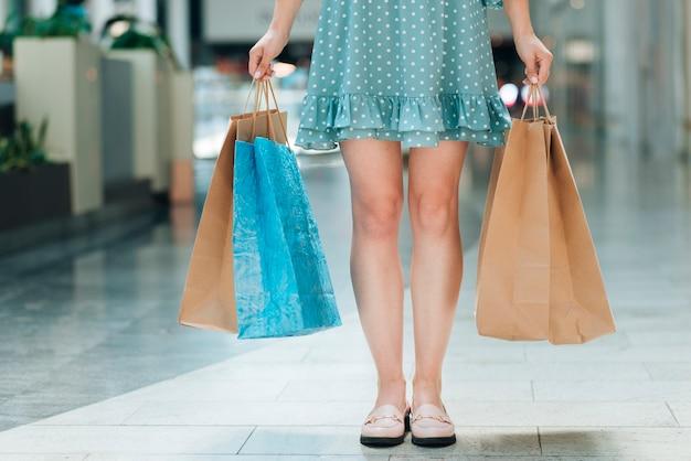 Vista frontal de la mujer con bolsas de la compra.