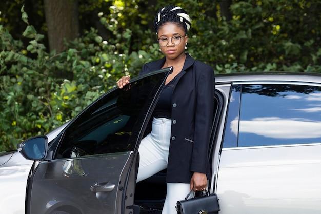 Vista frontal de la mujer con bolso entrando en su coche