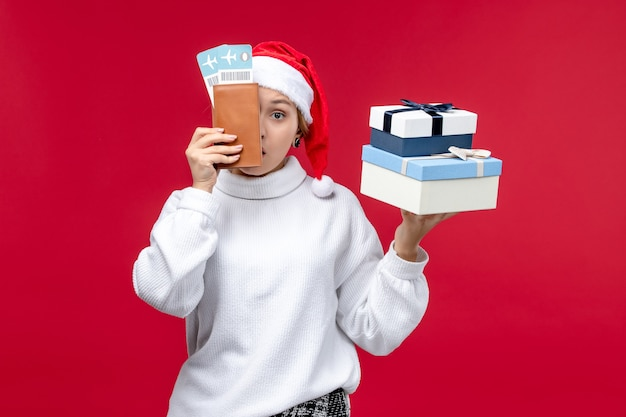 Vista frontal de una mujer bonita con entradas y regalos sobre fondo rojo claro