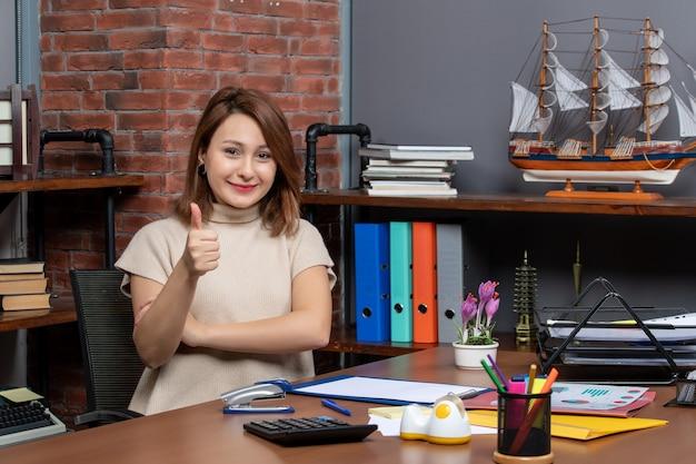 Vista frontal de una mujer bonita haciendo pulgar hacia arriba firmar trabajando en la oficina