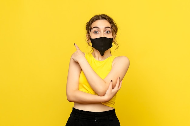 Vista frontal de la mujer bonita en máscara negra sobre amarillo