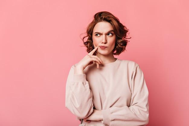 Vista frontal de una mujer bonita pensativa. chica rizada pensando en fondo rosa.