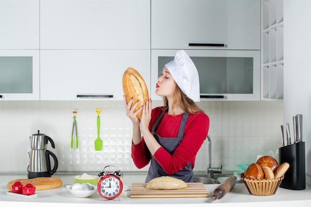Vista frontal de una mujer bonita con sombrero de cocinero y delantal oliendo pan en la cocina