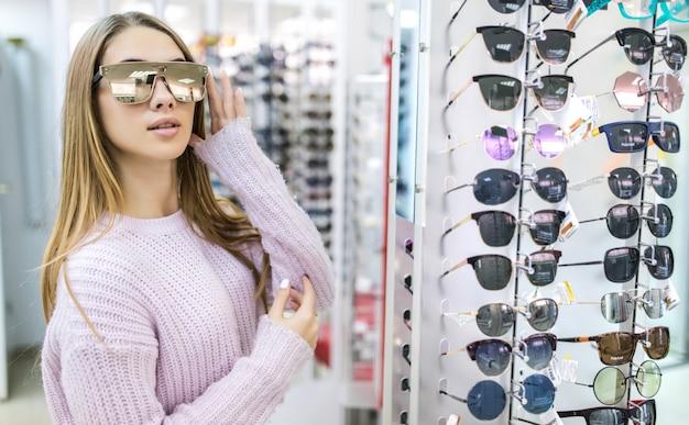 Vista frontal de una mujer bonita en suéter blanco pruebe gafas en tienda profesional en