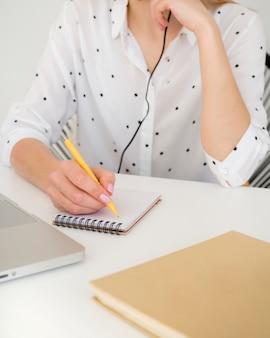 Vista frontal mujer en camisa blanca escribiendo