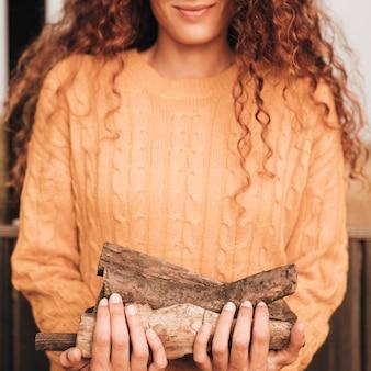 Vista frontal mujer cargando leña
