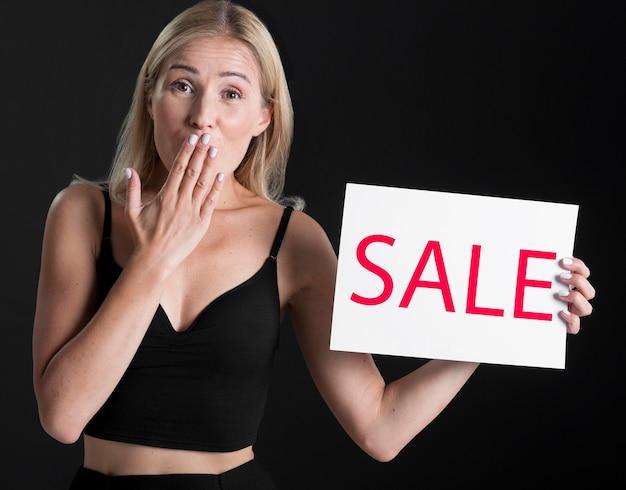 Vista frontal de la mujer con cartel de venta