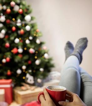 Vista frontal mujer en casa bebiendo té en navidad