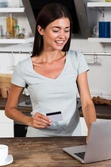 Vista frontal de la mujer en casa comprando en línea con computadora portátil y tarjeta de crédito