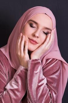 Vista frontal de la mujer cerrando los ojos mientras posa sobre fondo negro