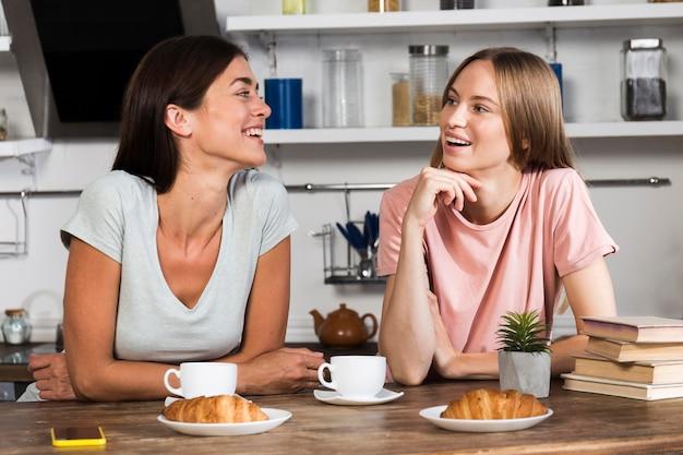 Vista frontal de la mujer charlando con café y croissants
