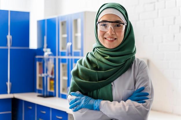 Vista frontal de la mujer científica con hijab posando en el laboratorio
