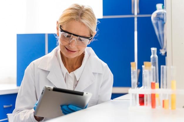 Vista frontal de la mujer científica en el laboratorio usando tableta