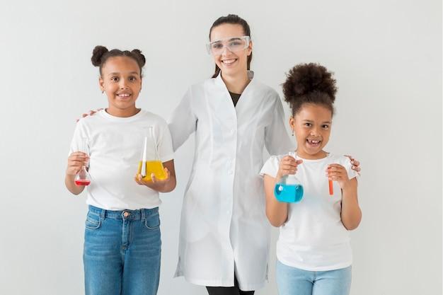 Vista frontal de la mujer científico posando con chicas jóvenes con tubos de ensayo