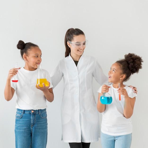 Vista frontal de la mujer científico posando con chicas sosteniendo pociones en tubos