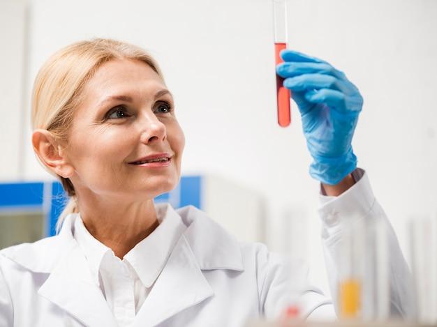 Vista frontal de la mujer científico con sustancia de laboratorio