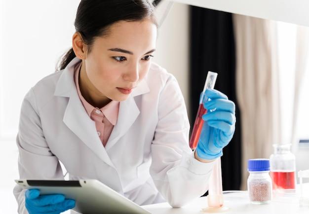 Vista frontal de la mujer científico con sustancia y tableta