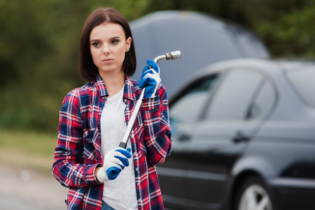 Vista frontal de la mujer con el coche en segundo plano.