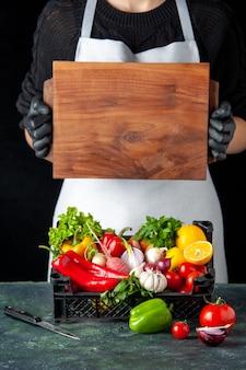 Vista frontal de la mujer cocinera con la canasta llena de verduras frescas en la cocina de color oscuro cocina ensalada de comida cocina