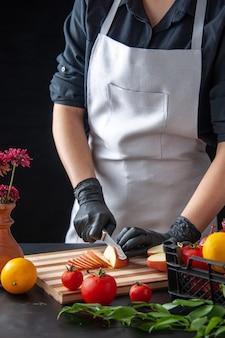 Vista frontal mujer cocinera cortando manzana en ensalada de cocina oscura trabajo de salud dieta comida vegetal comida frutas