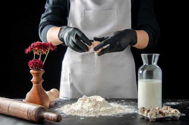 Vista frontal de la mujer cocinera rompiendo los huevos en harina en el trabajo oscuro pastel de pastelería panadería hornear pastel masa de galletas
