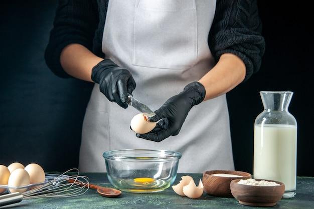 Vista frontal mujer cocinera rompiendo los huevos para la masa en pasteles oscuros pastel pastel panadería trabajador hotcake trabajo de cocina