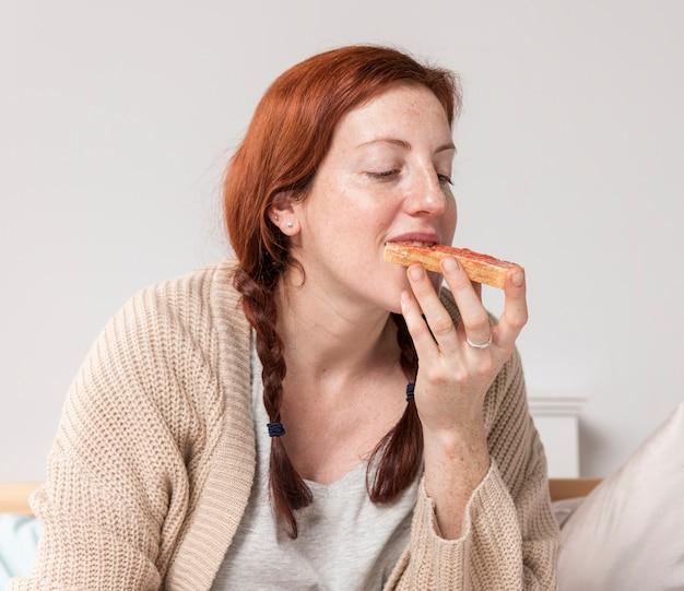 Vista frontal mujer comiendo delicioso desayuno