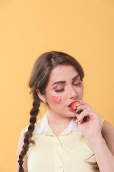Vista frontal de la mujer comiendo fresa con espacio de copia