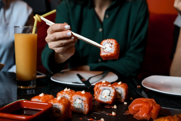 Vista frontal mujer comiendo sushi california rolls con jugo sobre la mesa