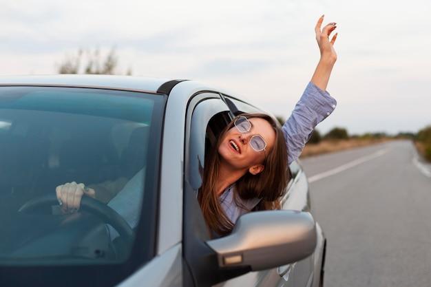 Vista frontal de la mujer conduciendo y divirtiéndose