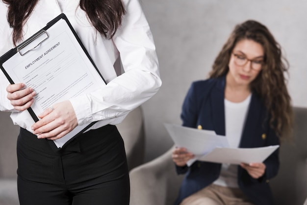Vista frontal de la mujer con contrato y otro leyendo documentos
