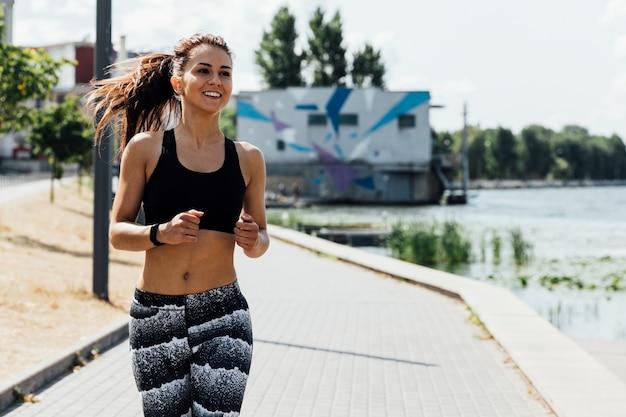 Vista frontal de la mujer corriendo