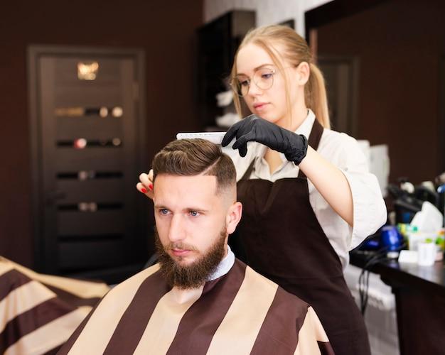 Vista frontal mujer cortando el cabello de un cliente