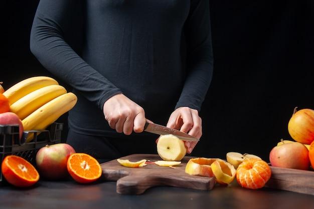 Vista frontal de la mujer cortando manzana fresca sobre tabla de madera frutas en bandeja de madera y caja de plástico en la mesa