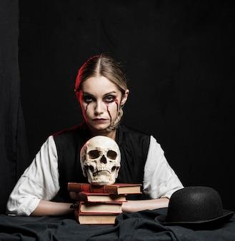 Vista frontal de la mujer con cráneo humano