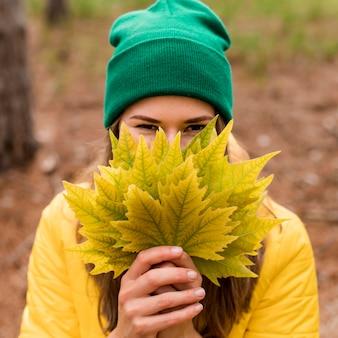 Vista frontal mujer cubriéndose la cara con un montón de hojas de otoño