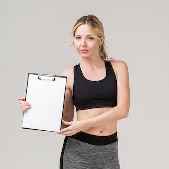 Vista frontal de la mujer deportiva posando mientras sostiene el bloc de notas