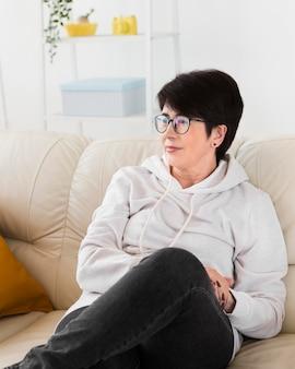 Vista frontal de la mujer descansando en su casa en el sofá