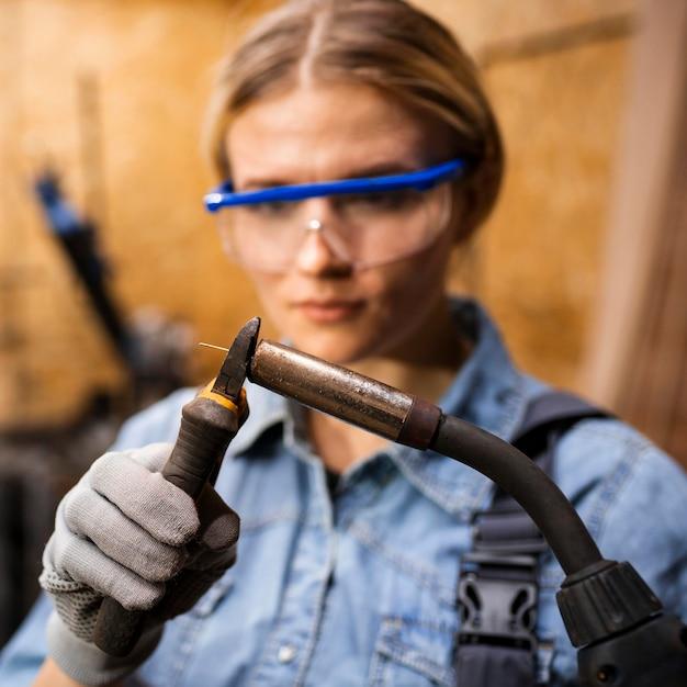 Vista frontal de la mujer con dispositivo de soldadura