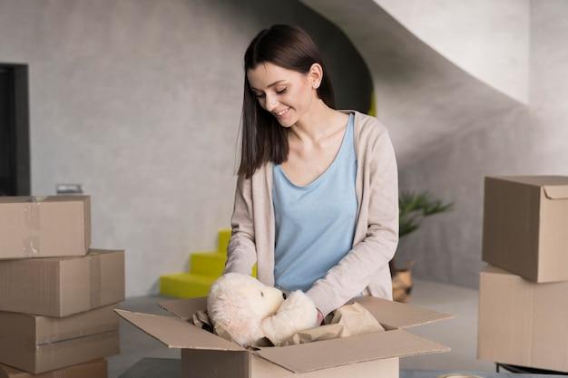 Vista frontal de la mujer embalaje oso de peluche en la caja de entrega